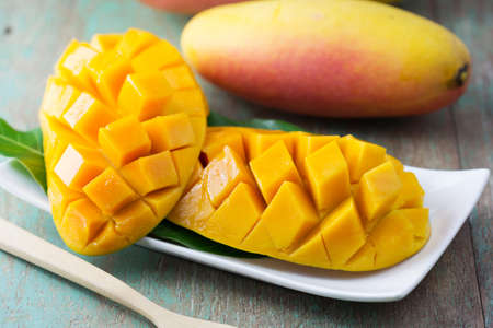 thai dessert: fresh mango fruit in white plate on wooden table Stock Photo
