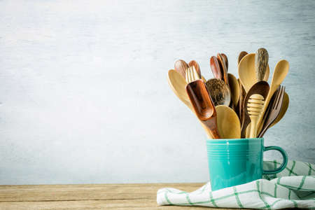 cooking implement: wooden kitchen utensils in cup on wooden background.
