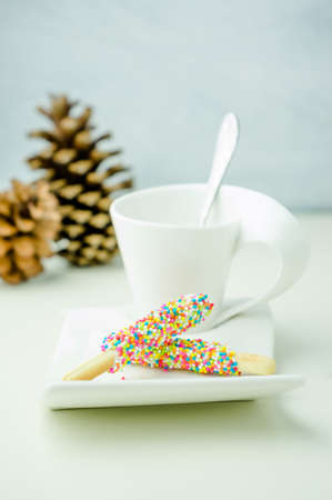 coated: Biscuit stick coated with rainbow and cup coffee
