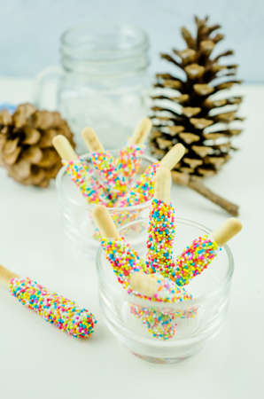 coated: Biscuit stick coated with rainbow in a glass