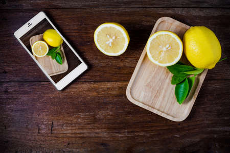 phon: Fresh slice lemons with leaves on wooden background. Stock Photo