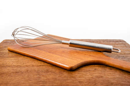 single whip: closeup whisk or egg beater on wooden table