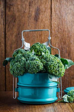 tiffin: Broccoli in metal tiffin on wooden background.