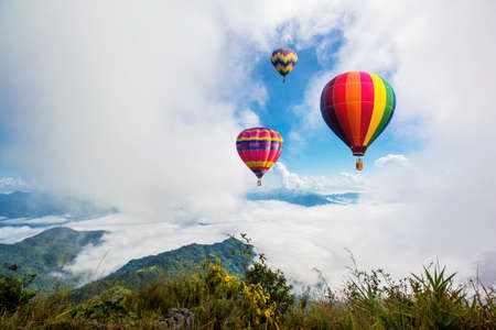 hotair: Colorful hot-air balloons flying over the mountain at Pha Tung,Chiangrai province ,North of Thailand. Stock Photo