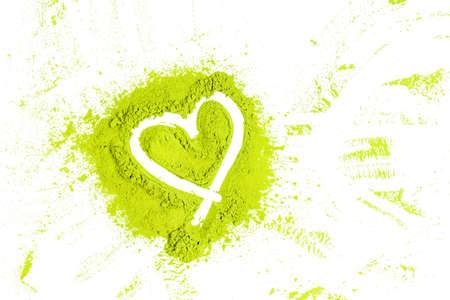 green powder forming heart shape surface close up on white background Stock Photo