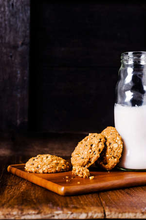 whole grains: Stack of whole grains cookies with milk bottle Stock Photo
