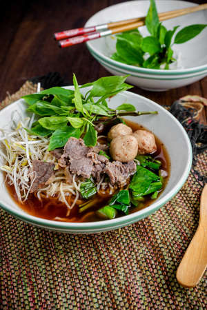 noodle soup: asian noodle soup with beef meatball with fresh vegetable on wood table vintage style, street food, hot and spicy noodle soup, asian food Stock Photo