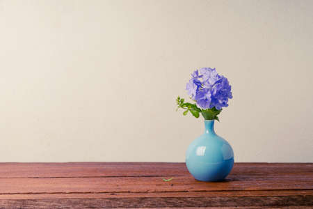 auriculata: Blue plumbago flowers in vase (Cape Leadwort or Plumbago auriculata) on wooden table. vintage tone.