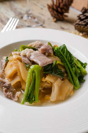 Fried noodle with pork and kale soaked in gravy, Thai Style food called Rad Na. Thai food