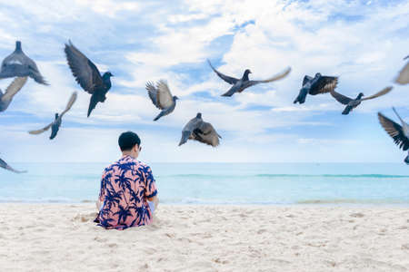 a young man sitting on the beach with Flying pigeons Stock Photo