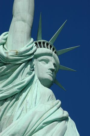 The Statue of Liberty reaches high on a clear blue skied day Stock Photo