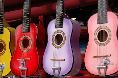 Four colourful toy guitars hang outside a small shop