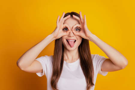 Photo of funny crazy lady two okey signs cover eyes protrude tongue wear white t-shirt posing on yellow background Фото со стока
