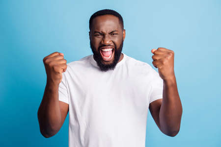 Cheering young man open mouth scream over blue background