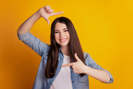 Closeup portrait of woman smiling make frame gesture isolated yellow wall background Imagens