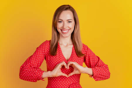 Portrait of charming lady formed a heart figure with the hands on yellow background