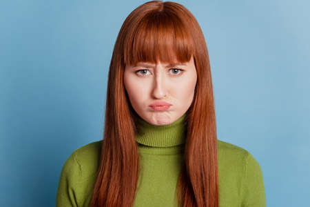 Photo of offended sad girl isolated over blue background