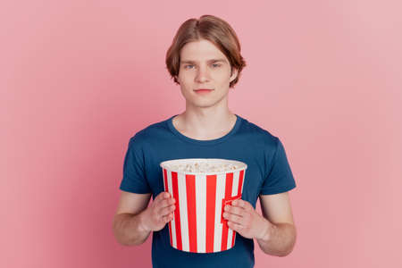 Photo of cheerful guy hold popcorn paper box happy positive smile watch tv film isolated pink color background
