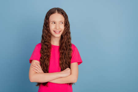 Portrait of successful little lady folded hands look side empty space on blue background