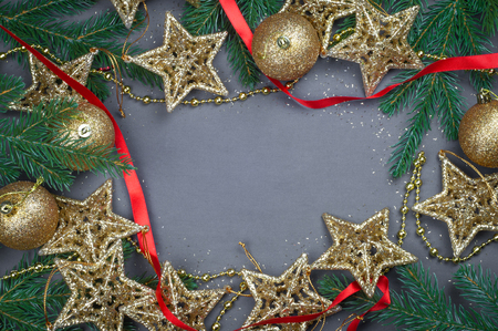 Christmas toys golden and red stars and balls a gray background with Christmas tree branches composition