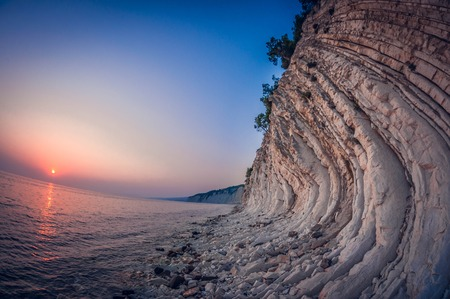 landscape white steep rocky layered seashore at sunset, fish eye distortion 免版税图像