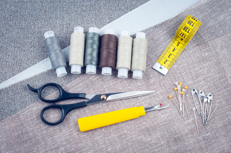 sewing pattern, composition with scissors, spools of thread, pins, measuring tape, Seam ripper, background of gray fabrics, top view