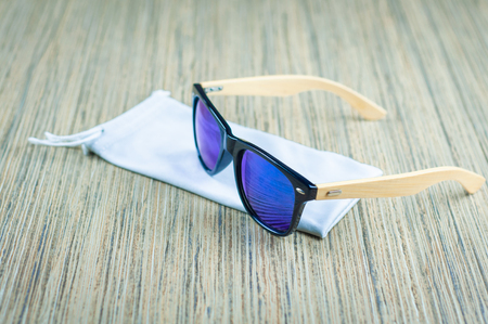 fashionable blue sunglasses in a rag cover are wooden on the table, wooden frame