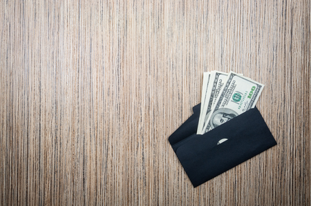 Dollars banknotes in a black envelope on a wooden table. top view, copy space Stock Photo