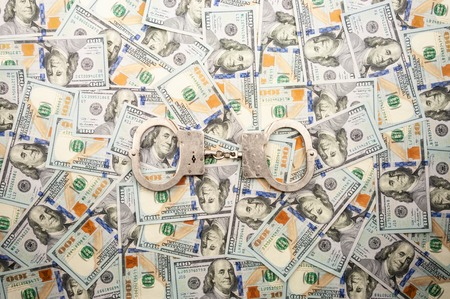 handcuffs lying on the background of dollars banknotes. top view 版權商用圖片 - 116341742