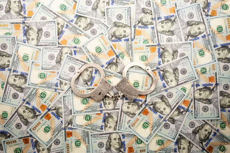 handcuffs lying on the background of dollars banknotes. top view