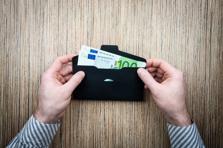 investing money euro in an envelope with male hands on wooden background. top view