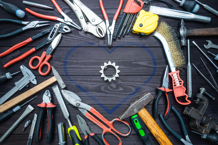 Tool and heart on a dark wooden background. Concept Love for your work, Father's Day.