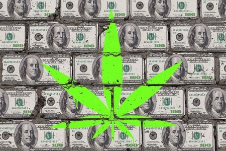 Painted cannabis leaf on the wall of dollars. Hemp business art concept.