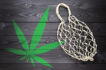 string bag of natural hemp with a marijuana leaf symbol on a dark wooden background.