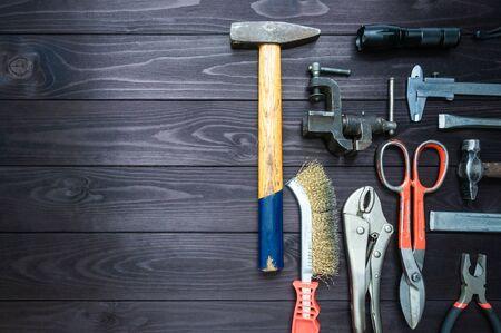 Hintergrund aus verschiedenen Werkzeugen auf einer dunklen Holzwerkbank. Ansicht von oben. Platz kopieren