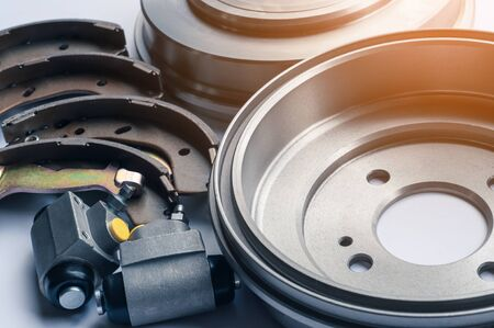New auto parts brake drums, pads and cylinders on a white background
