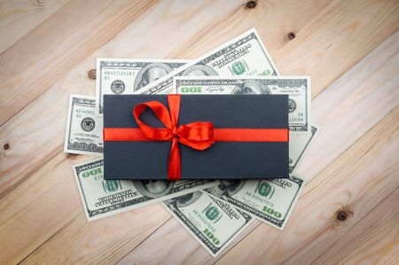Black gift box with hundred dollars banknotes on a light wooden table. top view