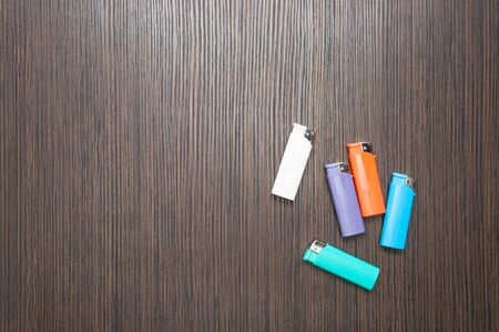 Multicolored lighters on a dark wooden table. top view