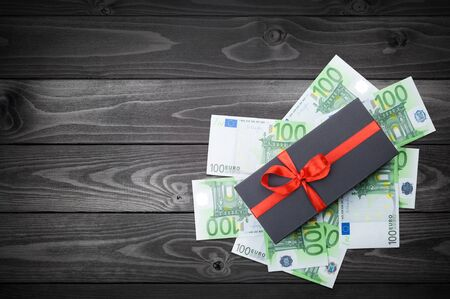 Black matte gift box with a bow with euro banknotes on a wooden table. top view, copy space