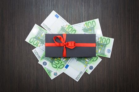 Black matte gift box with a bow with euro banknotes on a wooden table. top view
