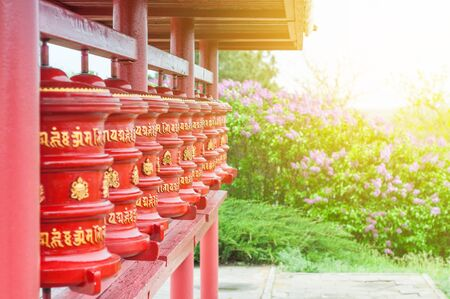 The prayer wheels with written untranslatable mantras. The religious symbol of Buddhism.