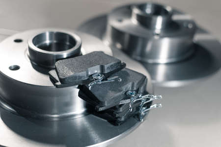 auto parts, new brake discs and pads in car service new brake discs and pads in the car service on the floor. Close up