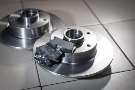 auto parts, new brake discs and pads in car service on the floor. Close up