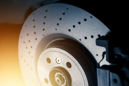 Installation of new perforated brake discs and pads on a modern auto in a car workshop. Close up. Blur effect.