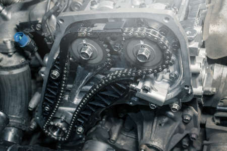 The new car timing chain on a disassembled diesel old engine in a car workshop. Close up. Blur effect.
