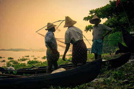 Kochi, Kerala, India – October 12, 2007 :  Three unidentified rural fishermen wearing Chinese style hats engaged in their day to day activity at the coast of Kochi, Rural people especially in southern part of India wear a typical dress called lungi that is wrapped around their waist area,