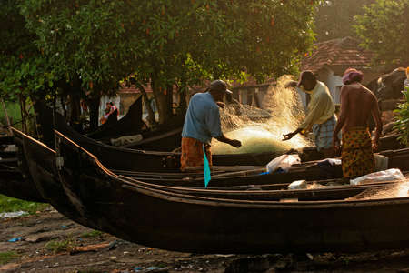 Kochi, Kerala, India – October 12, 2007 :  Some unidentified rural fishermen engaged in preparing their boat for fishing activity at the coast of Kochi; Rural people especially in southern part of India wear a typical dress called lungi that is wrapped around their waist area,