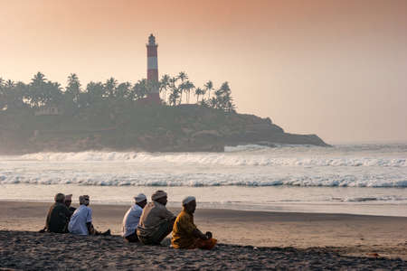 Kovalam, Kerala, India – October 17, 2007 :  Some unidentified local fishermen sitting prior to starting off their fishing activities at Kovalam coast in Kerala