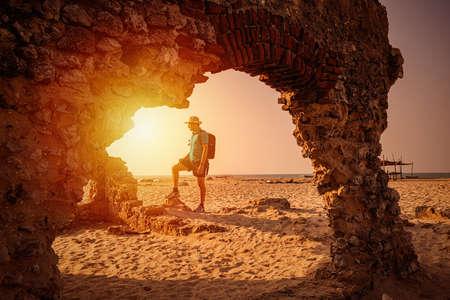 Traveler with backpack watching amazing sunset. Silhouette of the young man at dhanushkodi, Rameshwaram, Tamil Nadu, India. 免版税图像