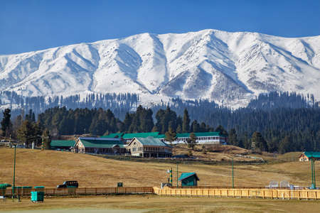 Hotels and resorts at foothills of Snow Covered Himalayan Mountains and Pine Tree Forests in Gulmarg, Jammu and Kashmir, India